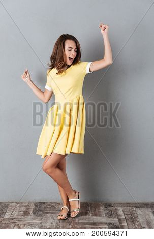 Full length portrait of a happy pretty girl in dress dancing isolated over gray background