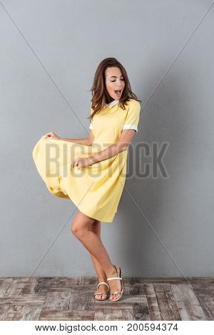 Full length portrait of a happy pretty girl in dress dancing and singing isolated over gray background