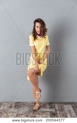 Full length portrait of an attractive young girl in dress posing on one leg isolated over gray background