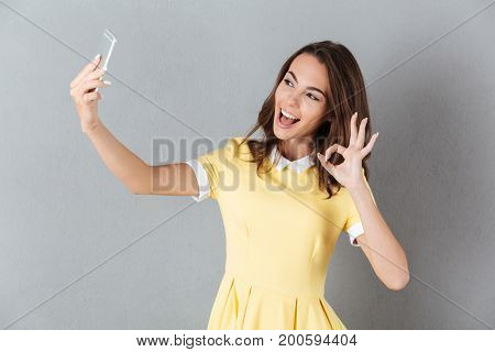 Pretty young girl showing ok gesture while taking a selfie with mobile phone isolated over gray background