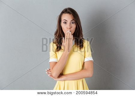 Surprised pretty girl in dress standing with her hand covering mouth and looking at camera isolated over gray background