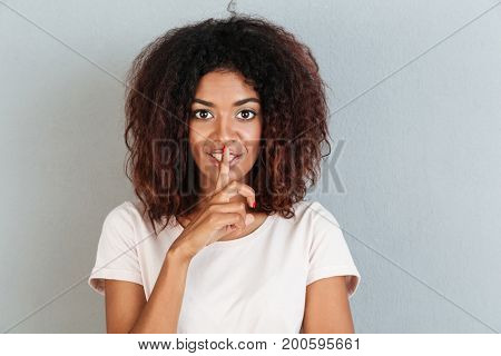 Smiling african woman showing silence gesture with finger on her lips isolated over white background