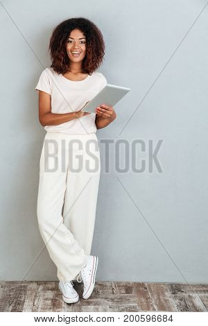 Full length of a casual smiling afro american woman standing and holding tablet computer isolated over white background