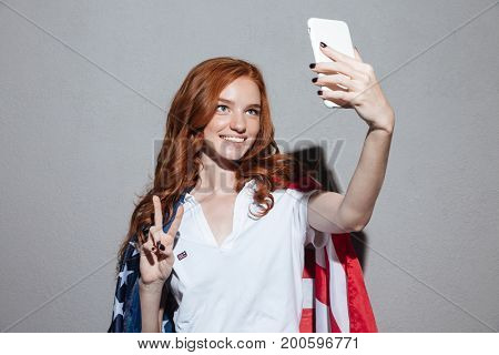 Picture of cheerful redhead young lady with USA flag make selfie by phone showing peace gesture. Looking aside.
