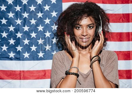 Picture of smiling african young woman standing over USA flag listening music in headphones. Looking camera.