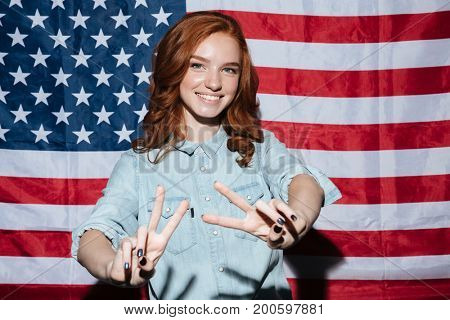 Image of cheerful redhead young lady standing over USA flag. Looking camera showing peace gesture.