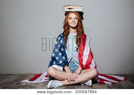 Image of happy redhead young lady holding book on head wearing USA flag. Looking camera.