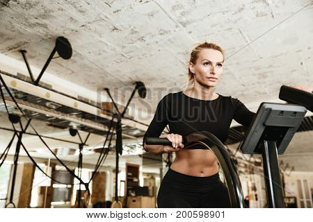 Picture of sports strong woman make sport exercise with spinning bicycle.