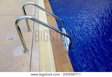 Soft focused picture of stainless steel Stairs down to the blue water in the pool