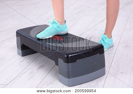 Young sporty woman training legs with stepper in gym