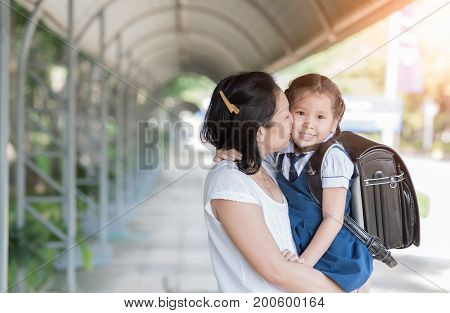 Mother kissing schoolgirl in uniform before going to school Love and care concept