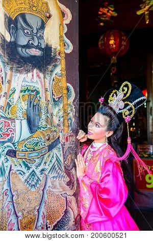 Chachoengsao Thailand - July 14 2013 : Beautiful woman with traditional chinese pink dress at Chinese shrine door with painting of ancient soldier in Thailand.