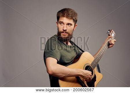 Man with a beard on a dark gray background holds a guitar, musical instruments, music, musician.
