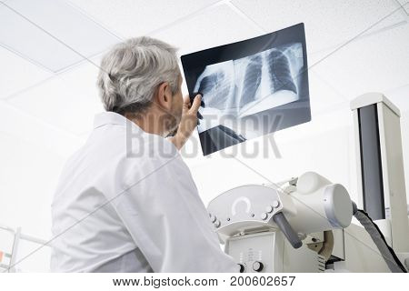 Male Doctor Analyzing Chest X-ray In Examination Room