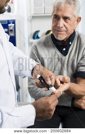 Doctor Checking Of Senior Patient's Sugar Level With Glucometer