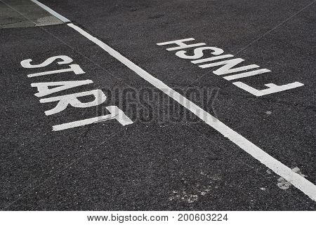 White painted Start and Finish line on tarmac with line diagonally across frame
