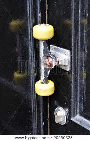 Skateboard wheels door handle on a black front door