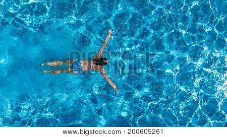 Aerial top view of woman in swimming pool water from above, tropical vacation holiday concept