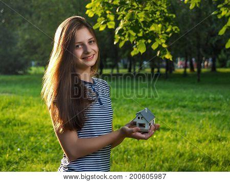 Girl holding house in hands. Green grass summer