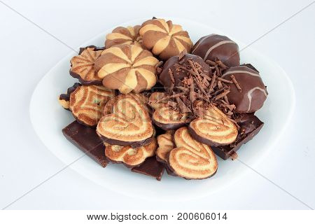 Marshmallow cookies and chocolate lying on a white plate. Sweet food.
