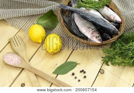 Fresh fish mullet in a basket and lemons on wooden table close-up.