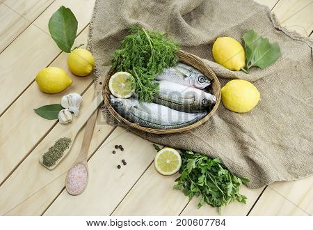 Fresh fish in a basket boops and lemons on wooden table close-up.