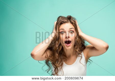The portrait of alarmed young woman with shocked facial expression