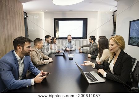 Perspective young businesspeople having meeting in conference room
