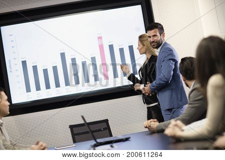 Young attractive businessman and businesswoman showing presentation to their colleagues in conference room