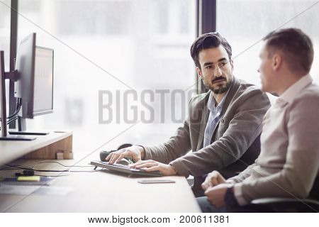 Picture of two young businessmen having discussion in office