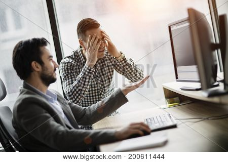 Picture of two young businessmen having problems in office
