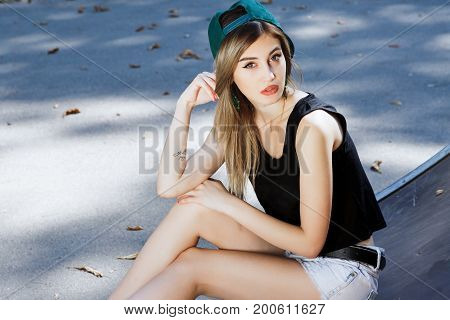 Attractive Blond Girl Sitting On The Pavement In The Skatepark