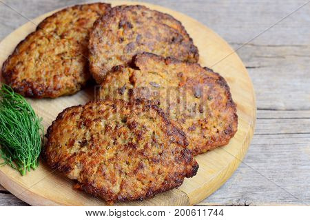 Chicken liver cutlets with vegetables. Home fried chicken liver cutlets on a wooden board. Chicken liver nutrition. Vintage wooden background. Rustic style. Closeup