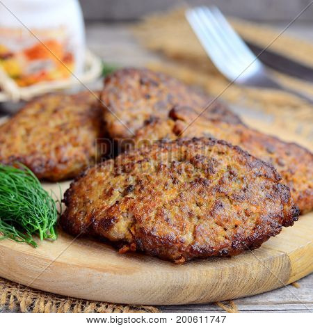Chicken liver cutlets with carrots and onions. Homemade fried chicken liver cutlets on a wooden board. Simple chicken liver recipe. Closeup