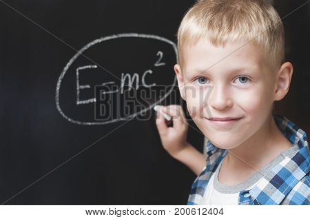 Boy writing formula of energy on the blackboard in classroom