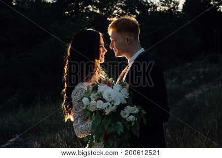 Newlyweds are standing and hugging outdoors, backlight, low key