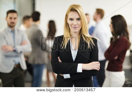 Business lady with positive look posing for camera in front of her colleagues