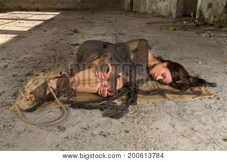 Depressed or scared young woman in rags lying on a dirty floor