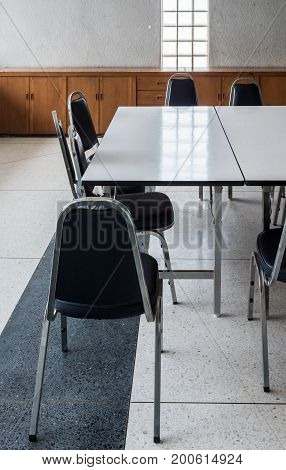 Large table and metal chair set for informal conference in the morning before the office hour outside the office building.