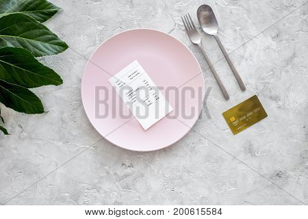 Meal is over. Bill on empty plate near bank card on grey stone table top view.