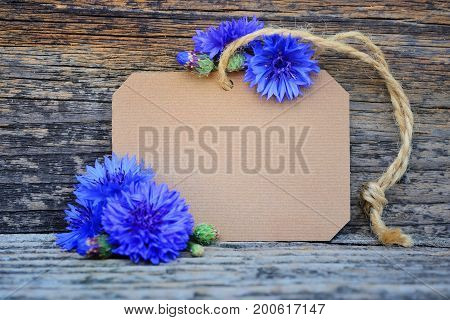 Paper Tag With Fresh Cornflowers (centaurea Cyanus) On Wooden Table