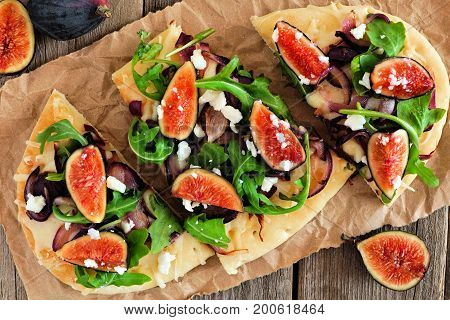 Flat Bread Pizza With Figs, Arugula, Caramelized Onions And Cheese, Overhead Scene On A Rustic Wood