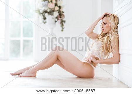 Beautiful sexy lady in white panties and bra. Close up fashion portrait of model indoors. Beauty blonde woman. Attractive female body in lace lingerie. Closeup fashionable naked girl in underwear
