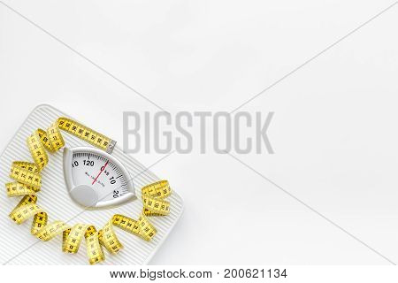 Bathroom scale and measuring tape on white background top view.