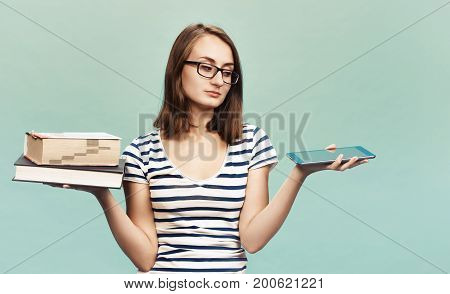 Book vs e-book. Girl student holding traditional textbook and ebook reader isolated on blue. The choice between paper books and education with electronic gadgets. Contemporary education concept. poster