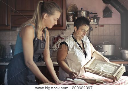 Mother and daughter preparing traditional food