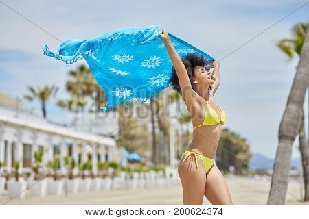 Happy Afro American Woman Holding Blue Shawl On Beach