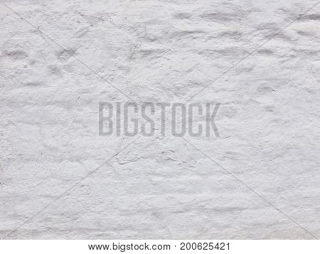 An old strong brick wall with a peeling white old cracked dirty paint