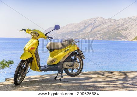 BRELA, CROATIA - 6 JULY, 2017: Yellow brand-less moped on the beach on a summer day.