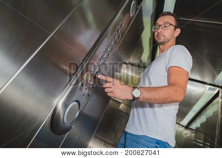 Young man in elevator pressing the zero floor button. Iron made interior.